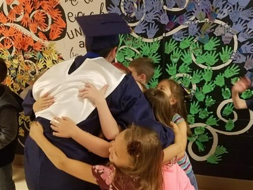 Student in cap and gown hugging younger students