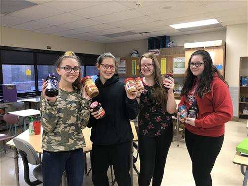 Students with peanut butter and jelly jars
