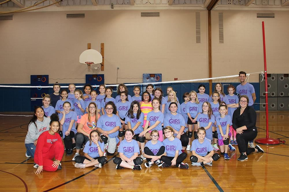 Girls and Coaches posing in front of Volleyball net.